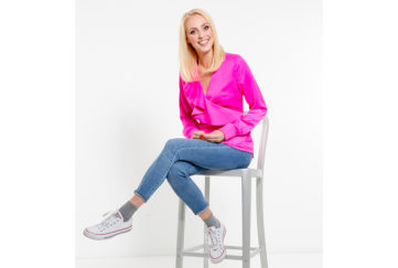 Happy slim blonde woman in bright pink top and blue jeans posing on stool, white background