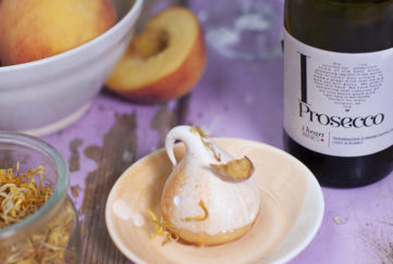 Meringue decorated with a petal and gold swirls, bowl of peaches and bottle of i heart prosecco