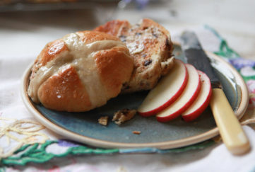 Toasted hot cross buns with butter and slices of Pink Lady apples