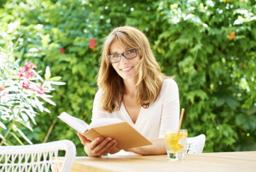 Woman sitting at patio table to read in the garden