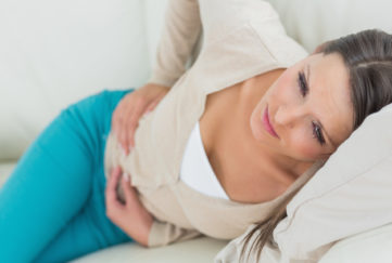 Woman lying on sofa with sore tummy