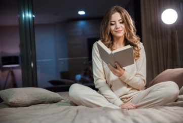Beautiful young curly woman in pajamas sitting on the bed and reading;