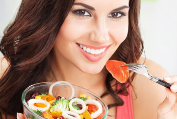 Dark haired woman eating salad