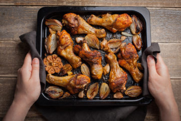 Female hands holding hot baking sheet from oven baked chicken legs with shallots and garlic. A woman puts on a dark wooden table with a tray of fried chicken.