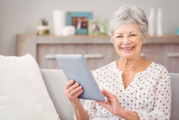 Mature woman holds up computer tablet and smiles
