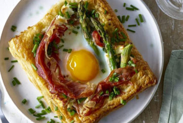 Square of golden puff pastry topped with baked egg, asparagus, melted feta cheese and herbs