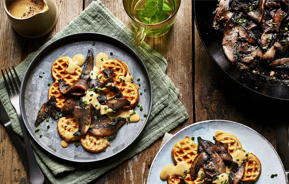 2 plates of small round golden waffles with rich brown mushrooms and creamy dressing