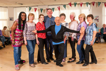 Ballet dancer Wayne Sleep in casual dancewear with 7 smiling mature ladies and one man at class run by Royal Voluntary Service