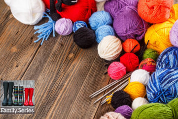 Knitting yarn balls in all colours and sizes on wooden floor, 2 pairs of knitting needles tucked between