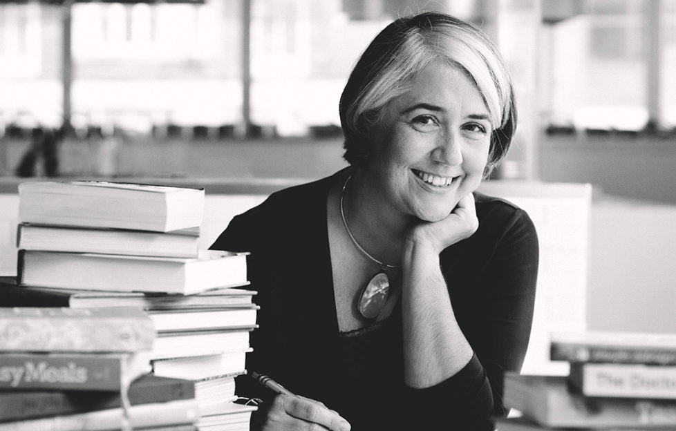 Black and white image, Alison Oakervee, stylish mature woman with part-blonde bob hairstyle, smiling and relaxed, at desk with pile of cookery books. Advice on how to freeze food