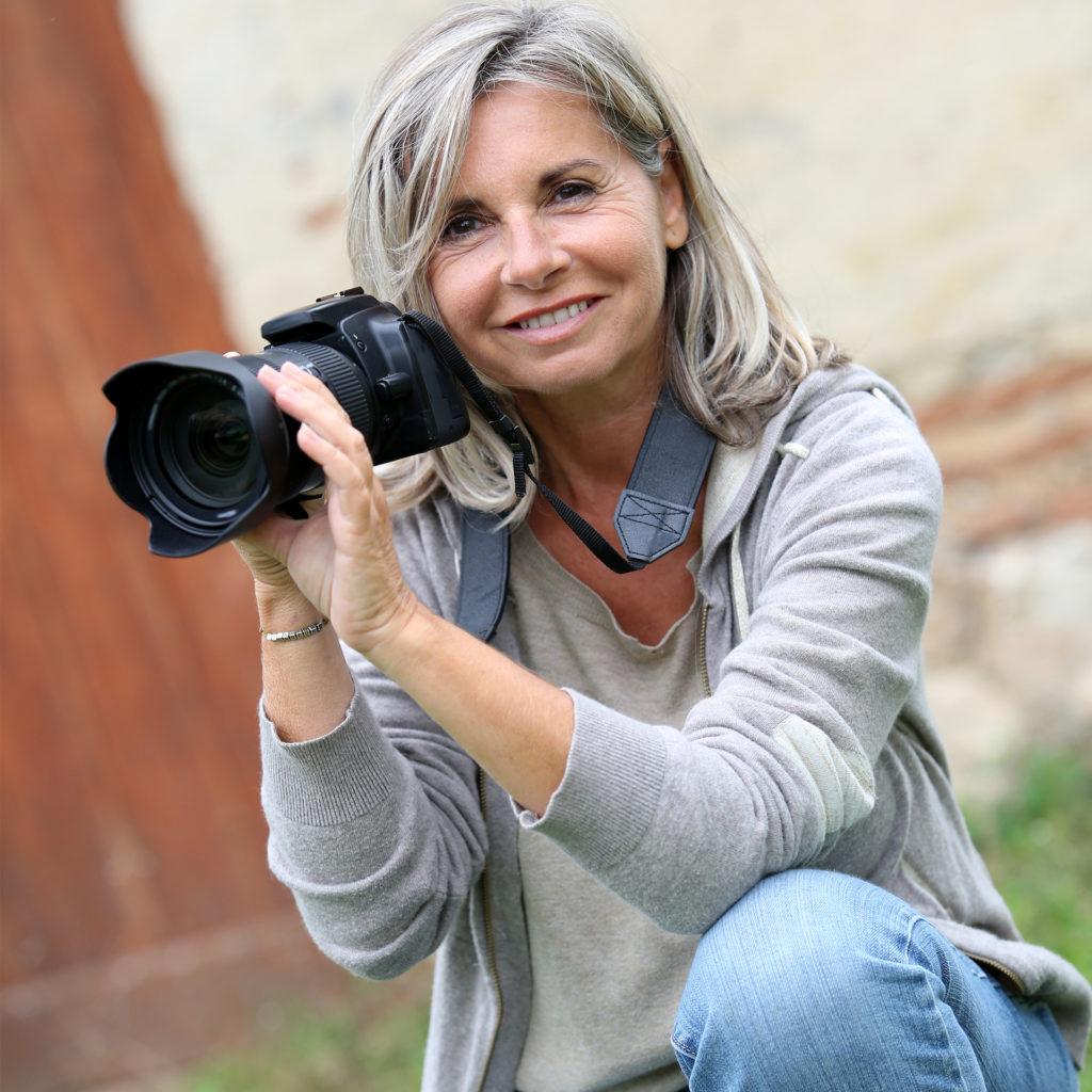 Mature woman kneeling, aiming professional camera