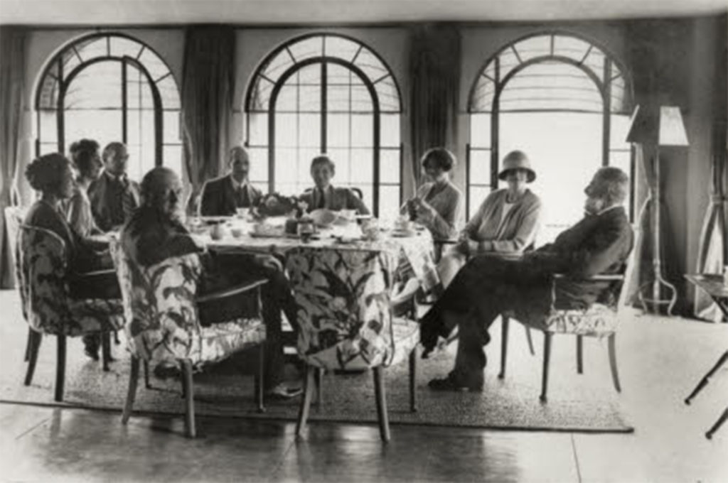 Black and white photo of people sitting around a table in front of 3 arched windows. One woman is wearing a cloche hat.