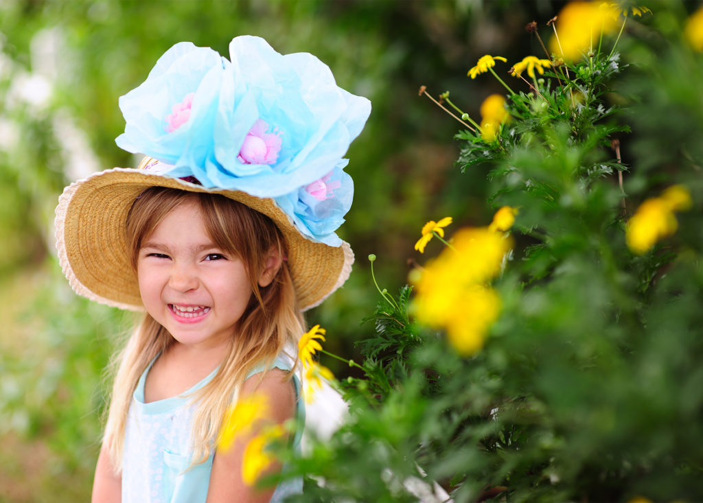 happy girl with straw hat and 3 huge blue and purple flowers, posing by yellow flowers