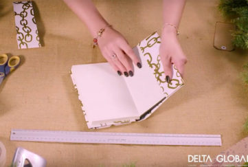 Woman covering book with decorative paper