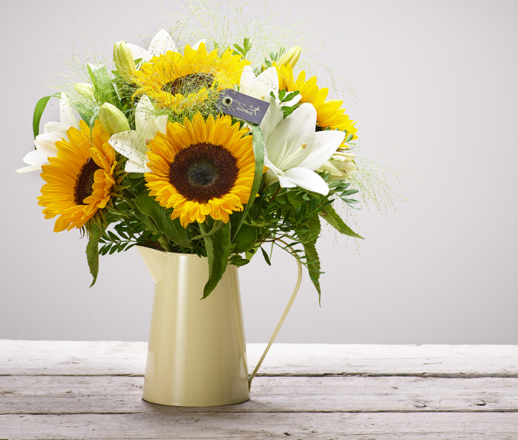 Bouquet with sunflowers and lilies in enamel jug on plain boards