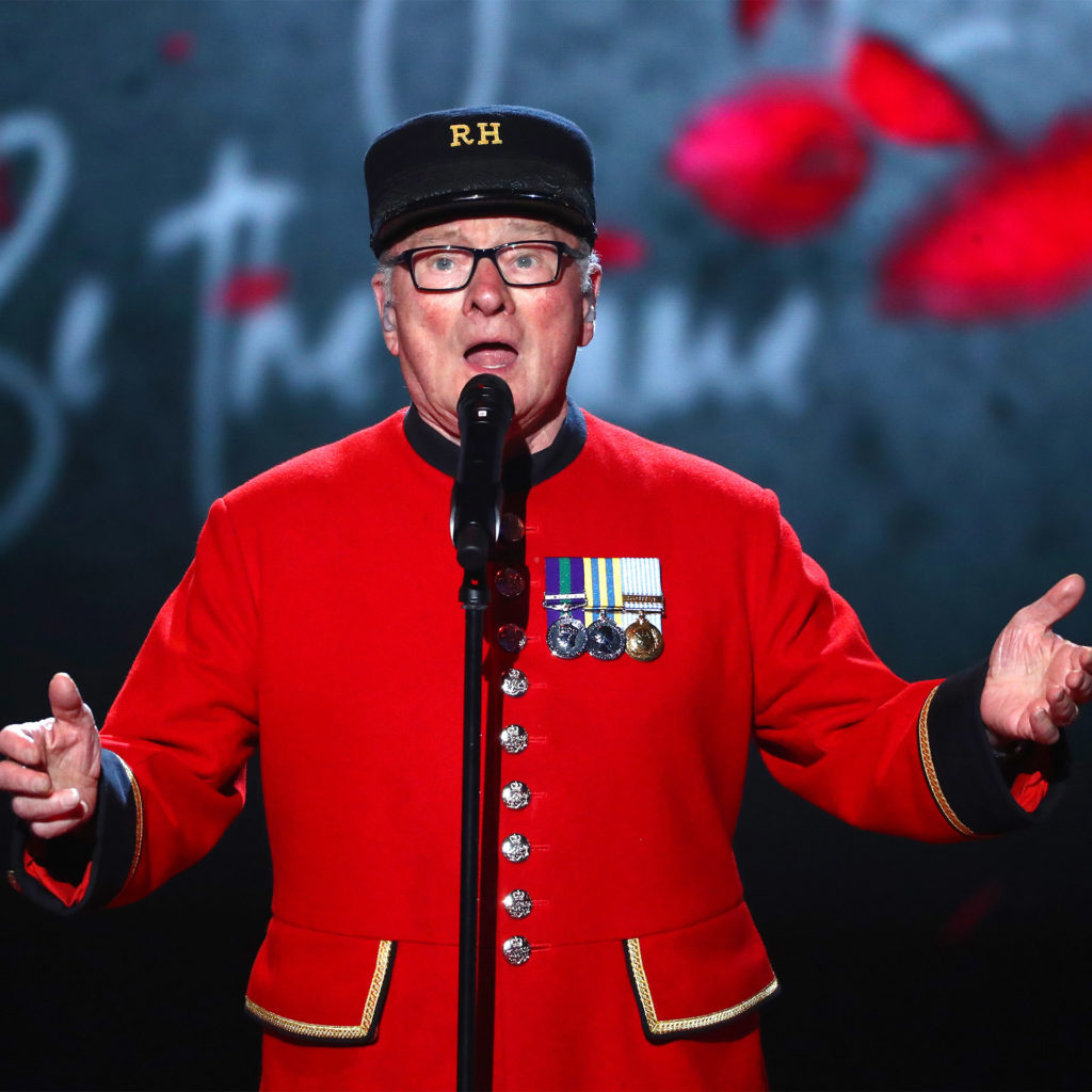 Britain's Got Talent winner Colin Thackery in his scarlet Chelsea Pensioner's uniform with medals, singing on stage with a backdrop of poppies and messages