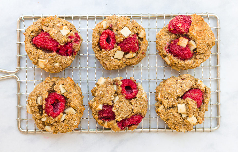 6 cookies on a wire tray, studded with raspberries and white choc chunks
