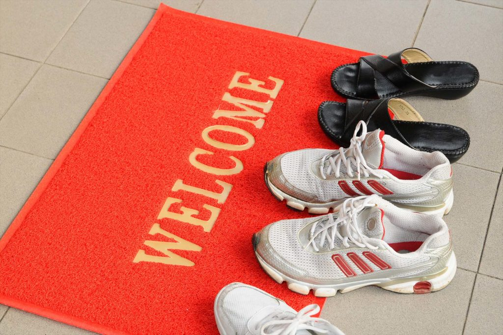Pairs Of Shoes On A Welcome Mat