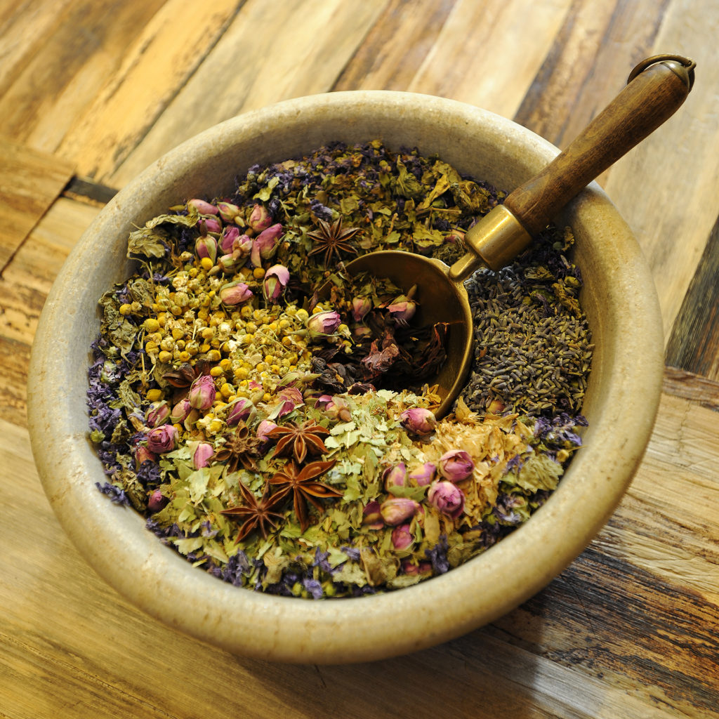 Beautiful bowl of dried herbs including rosebuds and chamomile heads, in a bowl with an ornate spoon