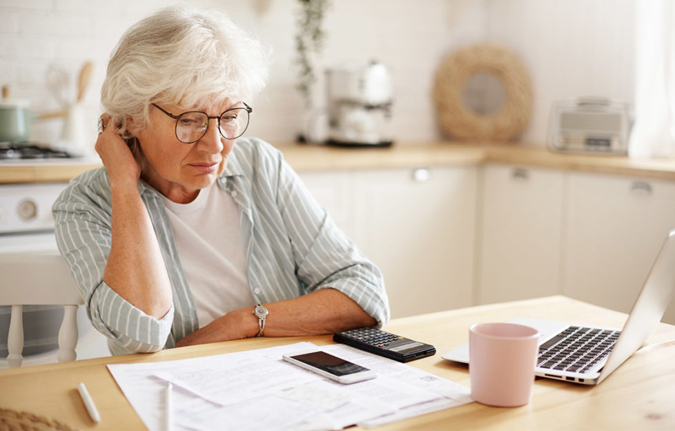 Mature woman at kitchen table sorting out finances with paper statements, phone, calculator and laptop, also mug of tea