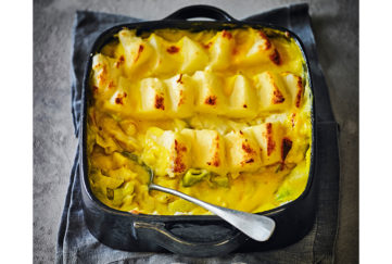 Black oven dish with handles, full of golden fish pie, mash on top arranged in stepped rows, fish and leeks in creamy golden sauce underneath