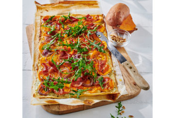 Rectangular pastry base with rich orange sliced sweet potatoes, onions and green rocket scattered over