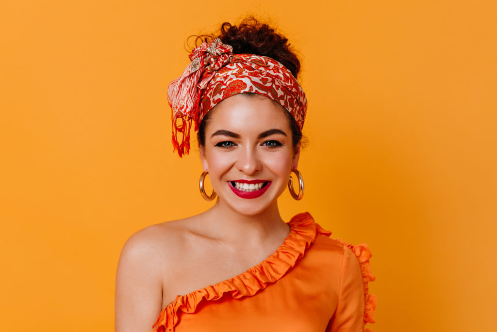 Happy woman with orange patterned silk scarf tied around head, hair visible above, orange background