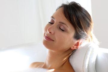 Woman relaxing in bubble bath, leaning head back on folded towel, eyes closed