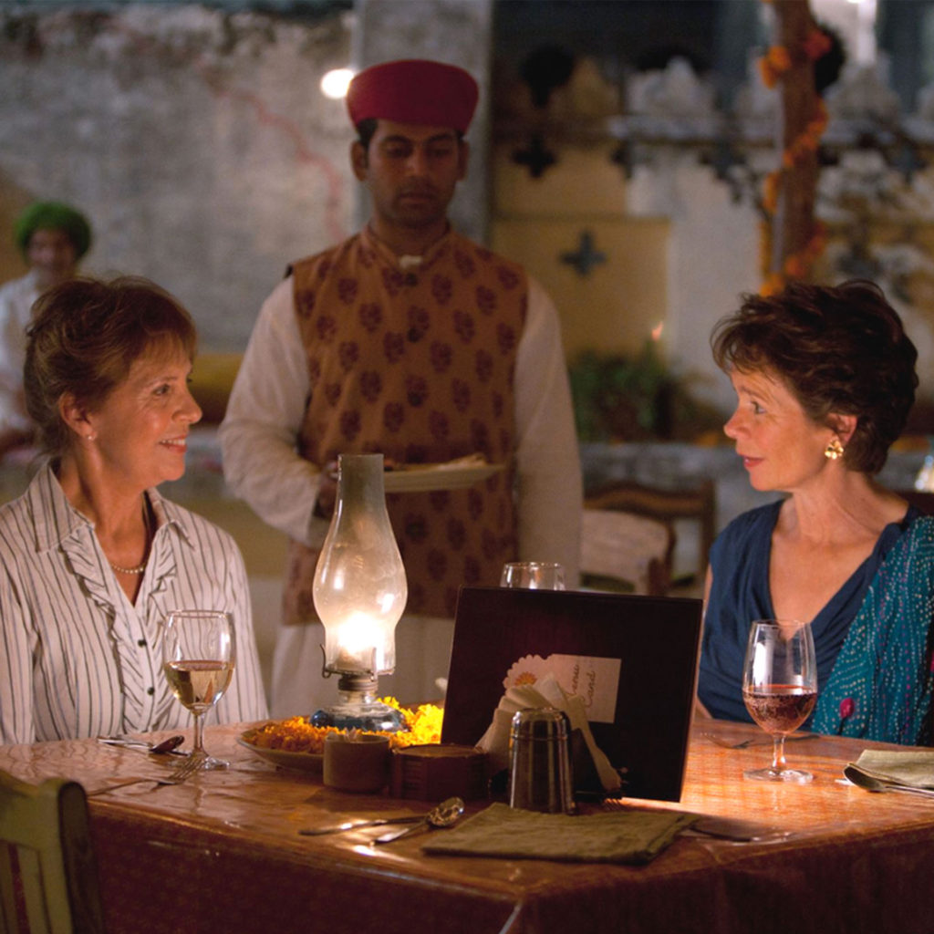 Penelope Wilon (left) and Celia Imrieat a table in a candlelit restaurant, man in Indian costume standing behind them