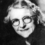 1958 photo of Georgina Landemare, smiling mature lady with grey hair pinned back and round glasses