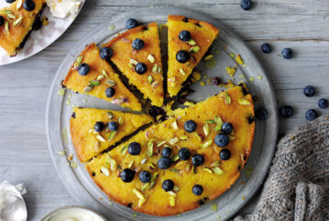Moist golden spongy cake topped with blueberries and pistachios, 5 slices cut, 1 on a plate