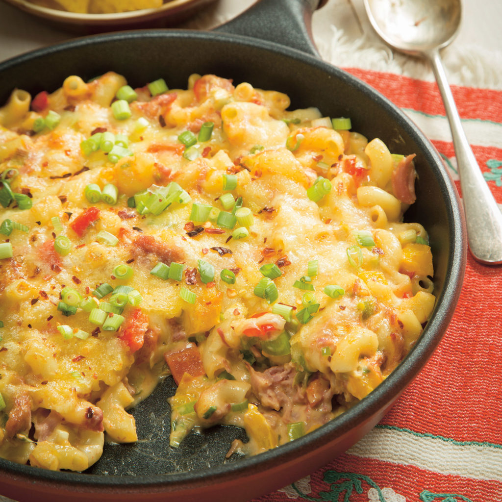 Pan of ranch macaroni cheese, topped with chopped spring onion and containing pulled pork and red pepper