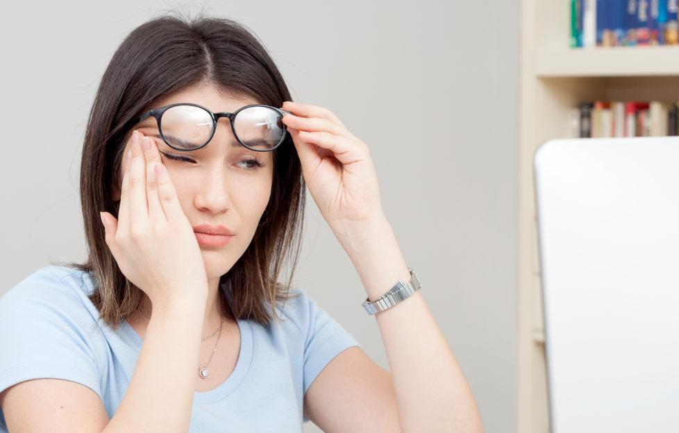 woman rubbing her eyes;