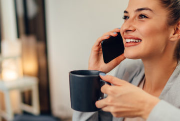 Happy young businesswoman wearing grey suit talking on the smartphone in the office and drinking coffee