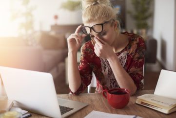 Blonde woman at laptop rubbing eyes, looking like she has a headache