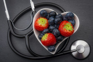 Healthy eating and heart health concept with a heart shaped bowl with blueberries and a stethoscope each blueberry is packed full of vitamins and antioxidants that can prevent coronary heart disease;