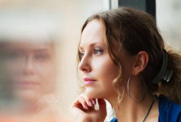Sad beautiful woman looking through a window;