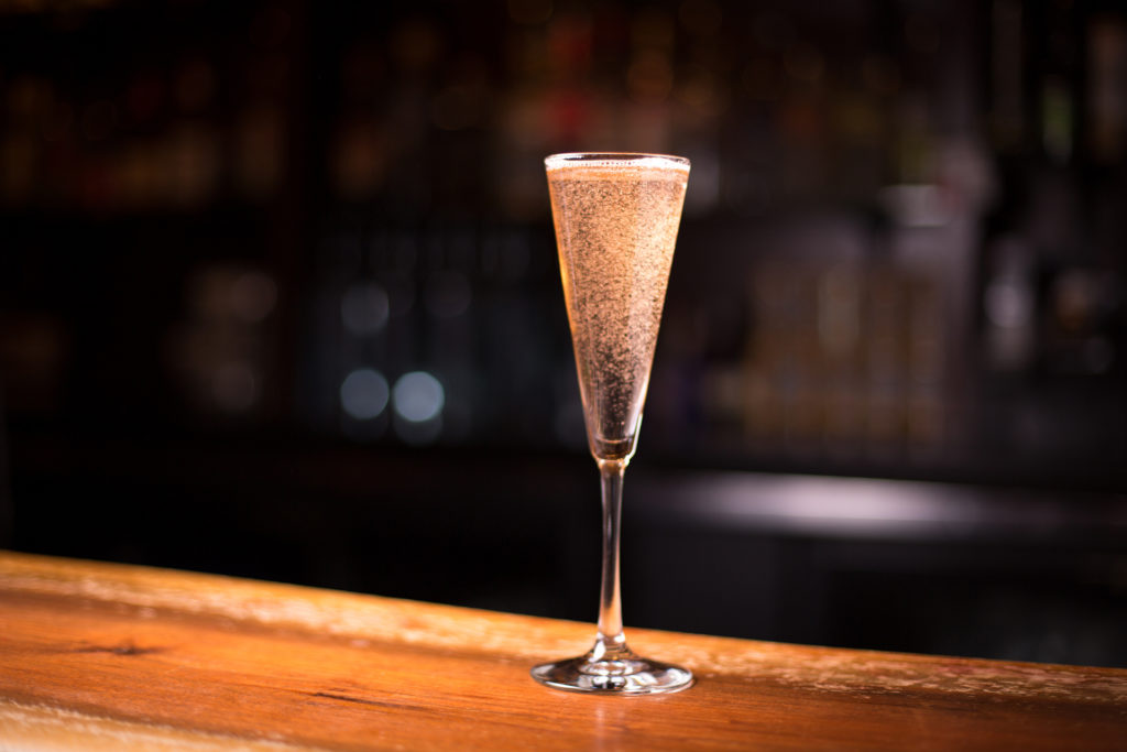 Low angle close up glass of sparkling champagne in traditional crystal flute stemmed wine glass with prosecco bubbles fizzing to surface in dramatic bar light happy hour drink restaurant scene;