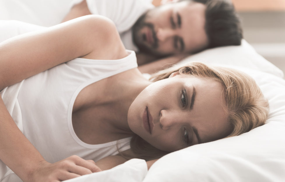 Anxious girl cannot sleep near her husband in bedroom;