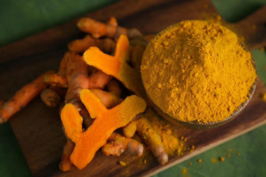 Fresh tumeric and tumeric powder on wood cutting board;