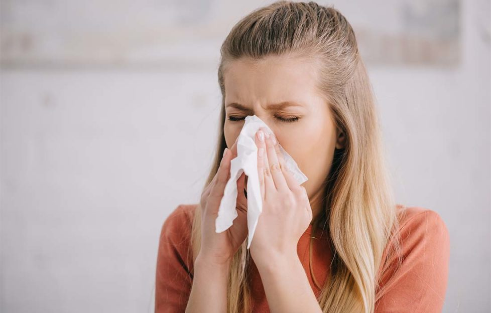 blonde woman sneezing while holding tissue near nose