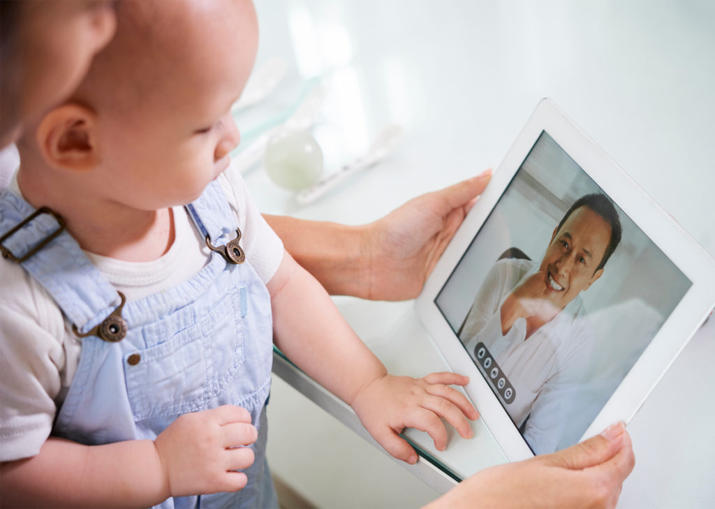 Parent and baby look at smiling young man on tablet screen