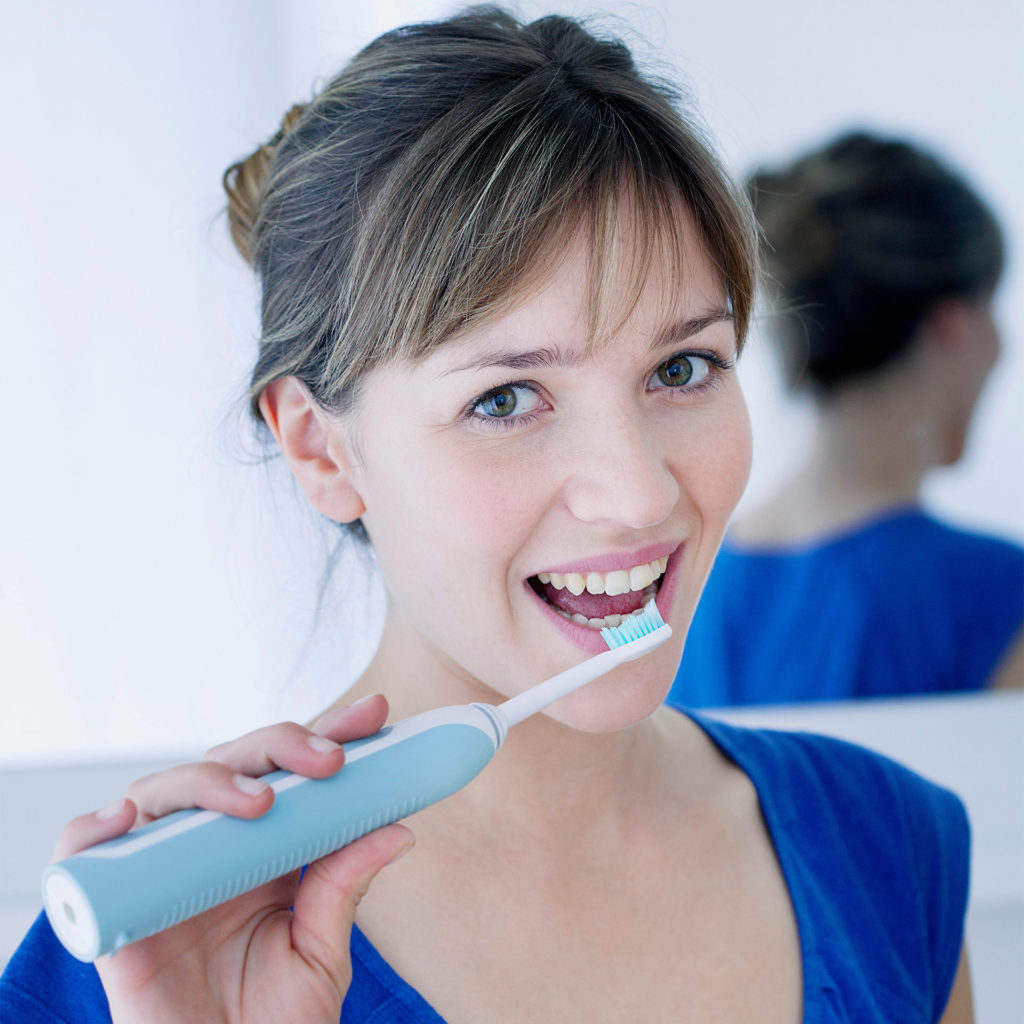 Young woman in blue top cleaning teeth with electric brush
