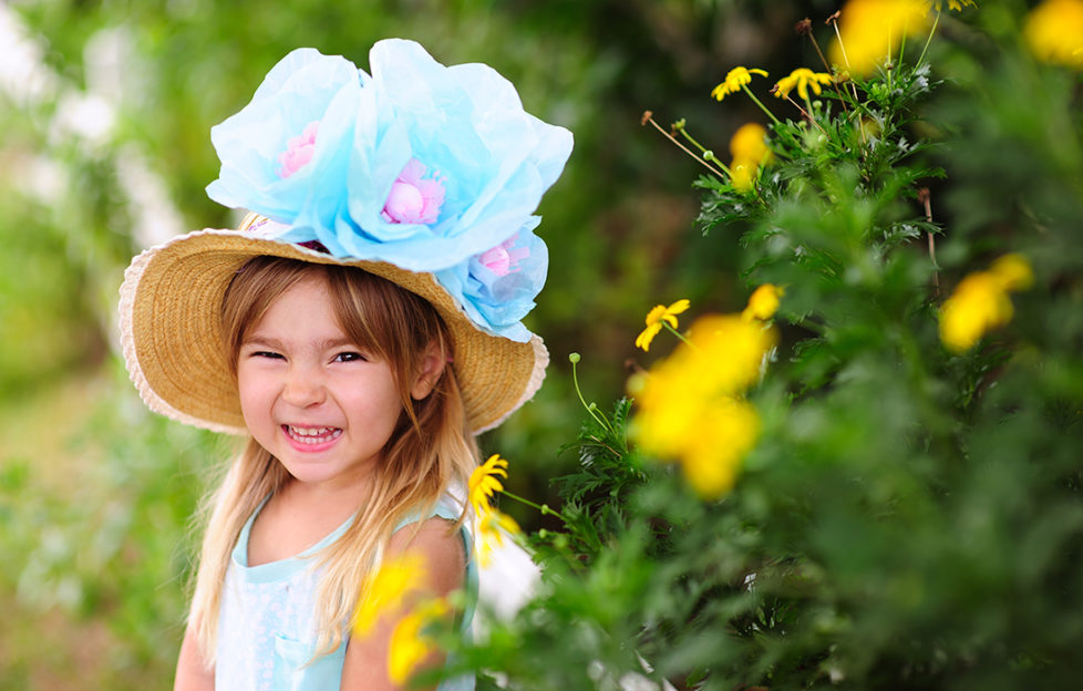 Happy girl with straw hat and 3 huge blue and purple flowers on it, Easter bonnet