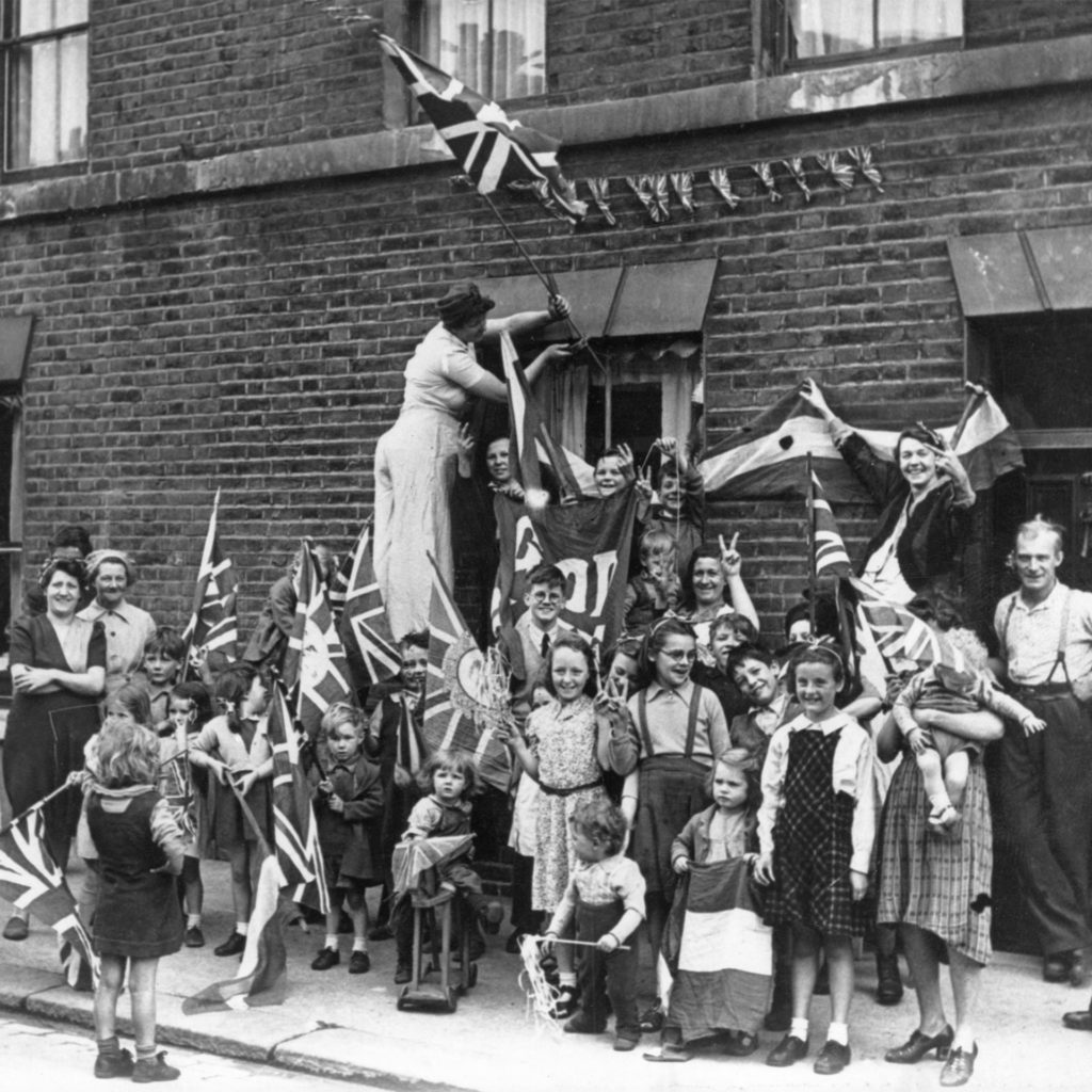 A crowd of people and children pose and smile while hanging out flags and bunting in Battersea, South London, to celebrate VE Day, 1945