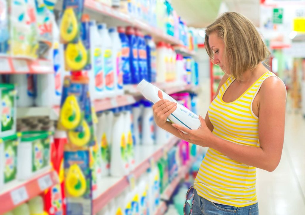Woman choosing laundry detergent in grocery store.