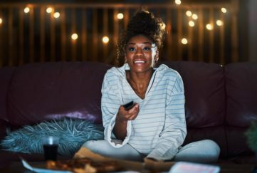 Woman smiling as she aims remote control at TV, night time city lights visible through window behind her