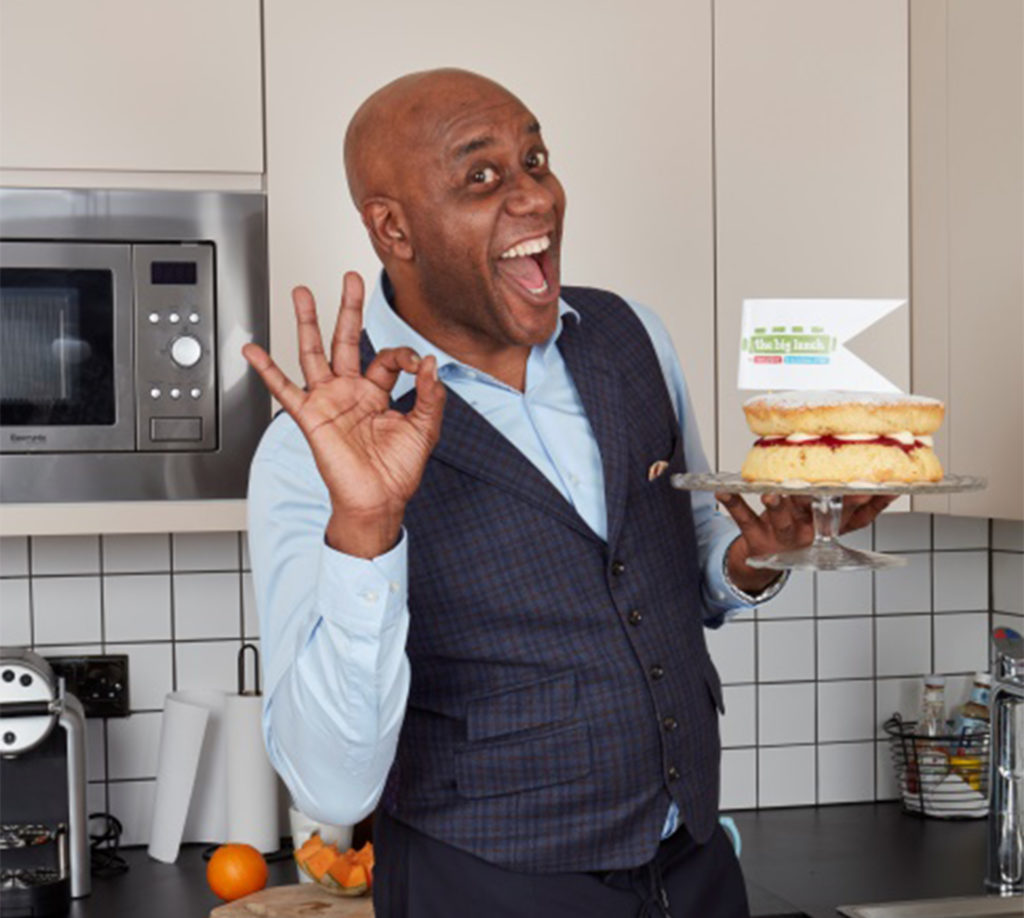 Celebrity chef Ainsley Harriott in his kitchenholds a sponge cake and gives a big grin and OK sign