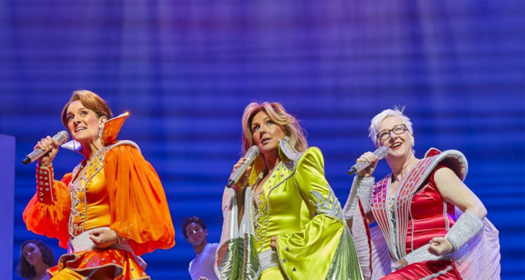 Three cast members of Mamma Mia on stage in the West End in 1970s stage outfits