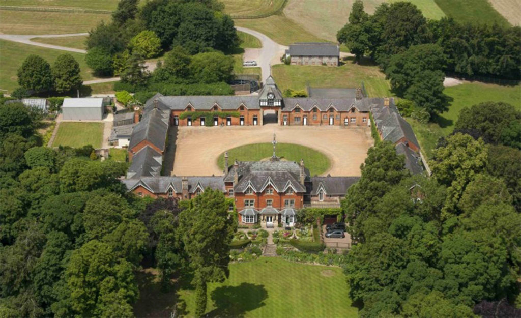 Aerial view of grand house with large courtyard and wooded grounds